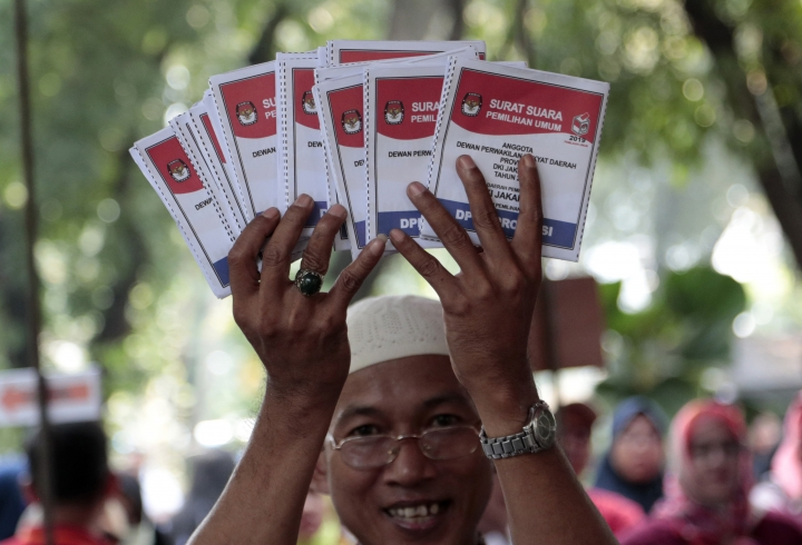 An electoral worker holds up ballots during a polling simulation exercise held by the election commission in Jakarta, Indonesia, Wednesday, April 10, 2019. When Indonesians vote in presidential and legislative elections next week, they'll be wrestling with choices affecting their country's future, and ballots as big as giant posters. (AP Photo/Dita Alangkara)