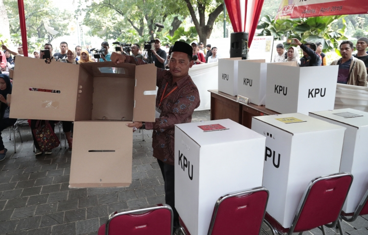 An electoral worker shows an empty ballot box during a polling simulation exercise held by the election commission in Jakarta, Indonesia, Wednesday, April 10, 2019. When Indonesians vote in presidential and legislative elections next week, they'll be wrestling with choices affecting their country's future, and ballots as big as giant posters. (AP Photo/Dita Alangkara)