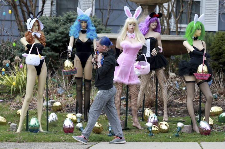 A woman walks carrying her dog past an Easter display in Clifton, N.J., Tuesday, April, 9, 2019. A New Jersey woman unhappy with her neighbor's racy Easter display used some garden shears to damage it. But the display's owner says it will soon be back up. The display at a dental office in Clifton featured five mannequins dressed in lingerie, all holding Easter baskets and surrounded by Easter eggs. It had drawn mixed reviews from neighbors, as well as passers-by who stopped to take photos. ( Ed Murray/NJ Advance Media via AP)