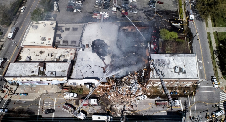In this aerial photo, firefighters battle a fire at the scene of an explosion in Durham, N.C. Wednesday, April 10, 2019. (Julie Wall/The News & Observer via AP)