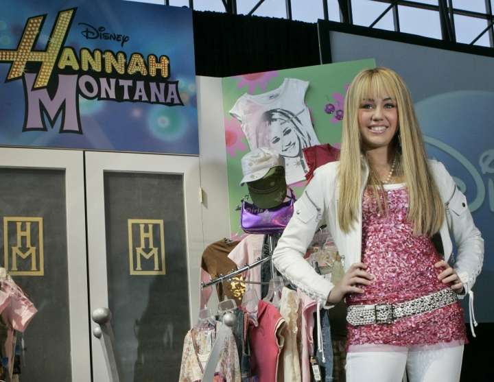 """FILE - In this June 19, 2007 file photo Miley Cyrus, star of The Disney Channel's series """"Hannah Montana"""" makes an appearance at the Licensing International Expo in New York. Costumes, props and tour items from the Disney Channel's """"Hannah Montana"""" TV series are going up for auction. The teen sitcom featured Cyrus, who portrayed schoolgirl Miley Stewart by day and international pop star Hannah Montana by night. It helped launched Cyrus' career and the franchise included albums, films and concerts. Julien's Auctions announced on Thursday, April 11, 2019, all proceeds will benefit the Wilder Minds charity, which aids the world's at-risk animals. (AP Photo/Mary Altaffer, File)"""