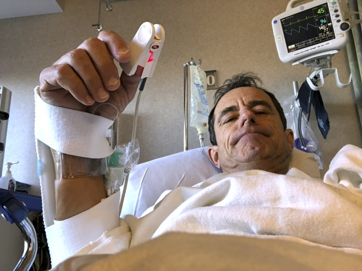 In this Sept. 5, 2018, photo provided by Katie McGillivray, Boston Marathon race director Dave McGillivray gives the thumbs-up after undergoing an angiogram at Massachusetts General Hospital in Boston. McGillivray, recovering from subsequent open-heart triple bypass surgery, is cautioning people thinking of running a marathon to talk with their doctors before hitting the road, especially if they have coronary artery disease or a family history of it. (Katie McGillivray via AP)