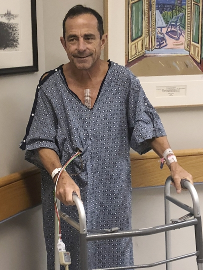 In this Oct. 14, 2018, photo provided by Katie McGillivray, Boston Marathon race director Dave McGillivray uses a walker after undergoing open-heart triple bypass surgery at Massachusetts General Hospital in Boston. McGillivray, a lifelong competitor, is cautioning people thinking of running a marathon to talk with their doctors before hitting the road, especially if they have coronary artery disease or a family history of it. (Katie McGillivray via AP)