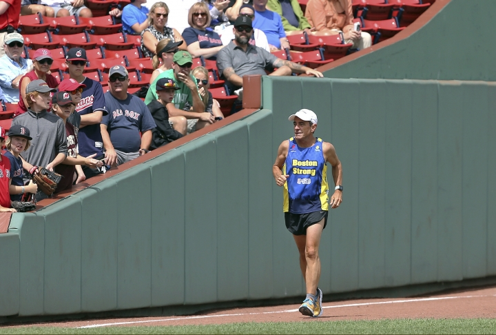 FILE - In this Aug. 23, 2018 file photo, Dave McGillivray, race director of the Boston Marathon, runs past fans inside Fenway Park, as he commemorates the last leg of his 80-day run in 1978 to benefit the Jimmy Fund, before a baseball game in Boston. A few months later, McGillivray underwent triple bypass surgery after suffering chest discomfort and difficulty breathing while running. He is cautioning people thinking of running a marathon to talk with their doctors before hitting the road, especially if they have coronary artery disease or a family history of it. (AP Photo/Elise Amendola, File)