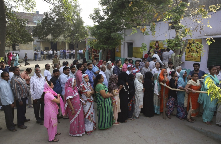 Indians stand in queues to cast their votes at a polling booth for the first phase of general elections, near Ghaziabad Thursday, April 11, 2019. Voters in 18 Indian states and two Union Territories began casting ballots on Thursday, the first day of a seven-phase election staggered over six weeks in the country of 1.3 billion people. (AP Photo/Manish Swarup)