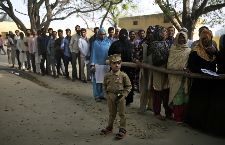 A young boy dressed as a policeman stands as Indians wait in a queue to cast their votes in village Sawaal near Meerut, Uttar Pradesh, India, Thursday, April 11, 2019. Voters in 18 Indian states and two Union Territories began casting ballots on Thursday, the first day of a seven-phase election staggered over six weeks in the country of 1.3 billion people.The election, the world's largest democratic exercise, is seen as a referendum on Prime Minister Narendra Modi and his Bharatiya Janata Party. (AP Photo/Altaf Qadri)