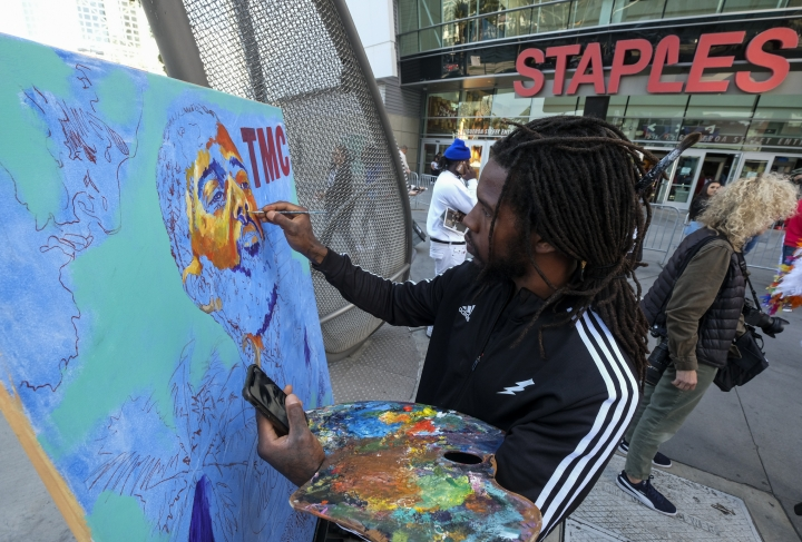 Artist Gift Davis works on a portrait of rapper Nipsey Hussle as fans wait in line to attend a public memorial at Staples Center in Los Angeles, Thursday, April 11, 2019. Hussle was killed in a shooting outside his Marathon Clothing store in south Los Angeles on March 31. (AP Photo/Ringo H.W. Chiu)