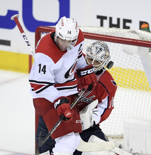 Carolina Hurricanes right wing Justin Williams (14) works for the puck against Washington Capitals goaltender Braden Holtby (70) during the third period of Game 1 of an NHL hockey first-round playoff series Thursday, April 11, 2019, in Washington. The Capitals won 4-2. (AP Photo/Nick Wass)