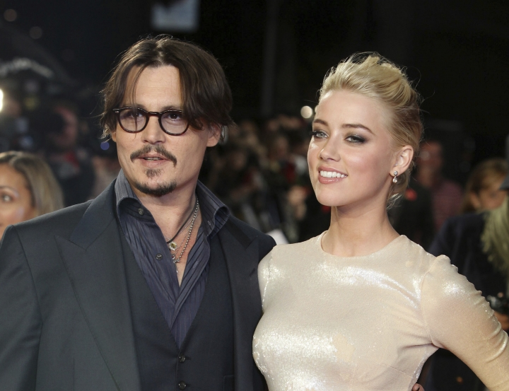 """FILE - In this Nov. 3, 2011 file photo, U.S. actors Johnny Depp, left, and Amber Heard arrive for the European premiere of their film, """"The Rum Diary,"""" in London.Heard is asking a judge to dismiss a $50 million defamation lawsuit her ex-husband Johnny Depp filed over a Washington Post op-ed she wrote about domestic violence. In the motion filed Thursday in Fairfax, Virginia, Heard's lawyers reiterate allegations that Depp abused her and include exhibits such as photos of her with bruised face and scarred arms. (AP Photo/Joel Ryan, File)"""