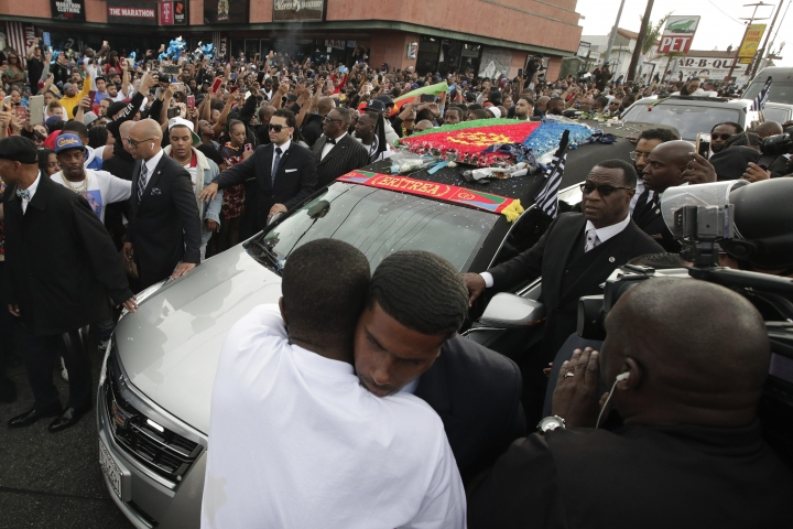 Two men hug as a hearse carrying the casket of slain rapper Nipsey Hussle passes through the crowd Thursday, April 11, 2019, in Los Angeles. The 25-mile procession traveled through the streets of South Los Angeles after his memorial service, including a trip past Hussle's clothing store, The Marathon, where he was gunned down March 31. (AP Photo/Jae C. Hong)