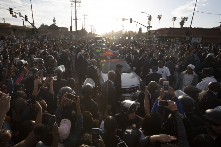 A hearse carrying the casket of slain rapper Nipsey Hussle passes through a large crowd on its 25-mile trek through the streets of the city Thursday, April 11, 2019, in Los Angeles. Hussle was shot and killed March 31 outside his The Marathon clothing store in South Los Angeles. (AP Photo/Jae C. Hong)