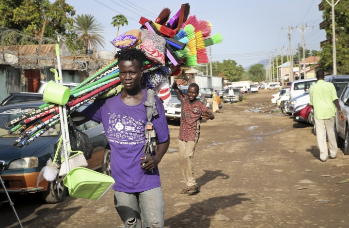 In this photo taken Thursday, April 11, 2019, a young merchant carrying brooms to sell walks along a street after the recent ousting of Sudan's President Omar al-Bashir, in the capital Juba, South Sudan. The military overthrow of Sudan's longtime president quickly has raised concerns about whether the upheaval will destabilize neighbouring South Sudan's fragile efforts at peace after five years of civil war. (AP Photo/Sam Mednick)