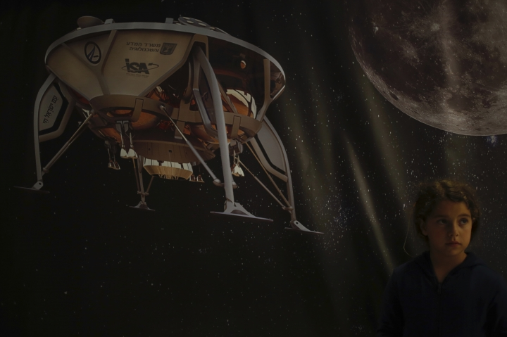 A girl poses for a photo next to a poster of the SpaceIL spacecraft in Netanya, Thursday, April 11, 2019. An Israeli spacecraft has failed in its attempt to make history as the first privately funded lunar mission.The SpaceIL spacecraft lost contact with Earth late Thursday, just moments before it was to land on the moon, and scientists declared the mission a failure. (AP Photo/Ariel Schalit)