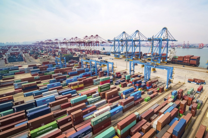 In this March 8, 2019, photo, trucks move at a container port in Qingdao in eastern China's Shandong Province. Data released Friday, April 12, 2019, shows that China's exports rebounded from a contraction in March and sales to the United States grew strongly despite President Donald Trump's tariff hikes.(Chinatopix via AP)