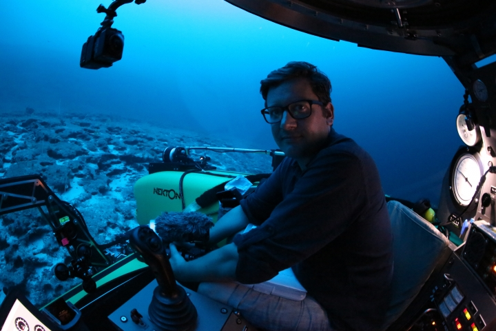 Associated Press reporter, David Keyton poses for a photograph inside a submersible at around 400 feet below the surface off the coast of the island of St. Joseph in the Seychelles, Monday April 8, 2019. Able to operate down to 1,000 feet, these manned submersibles give scientists a unique understanding of changes in habitats as sunlight diminishes through the different layers of ocean. (AP Photo/Robert Carmichael)