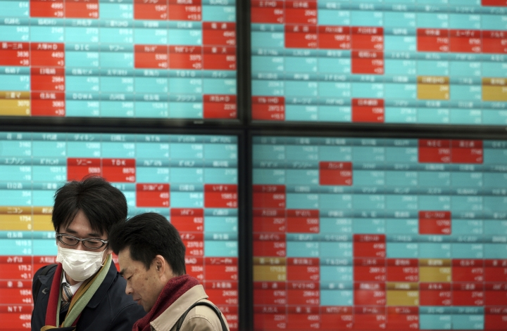 In this Feb. 19, 2019, photo, people talk in front of an electronic stock board showing Japan's Nikkei 225 index at a securities firm in Tokyo. Asian stock markets were mostly higher Friday, April 12, 2019, after a mixed Wall Street close on listless trading.(AP Photo/Eugene Hoshiko)