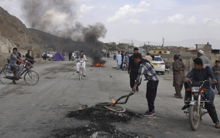 Pakistani Shiite youth from Hazara community burn tires to block a main road during a protest to condemn Friday's suicide bombing, in Quetta, Pakistan, Saturday, April 13, 2019. A suicide bomber targeted an open-air market in the southwestern Pakistani city of Quetta on Friday, killing many people and wounding dozens of others, police and hospital officials said. (AP Photo/Arshad Butt)