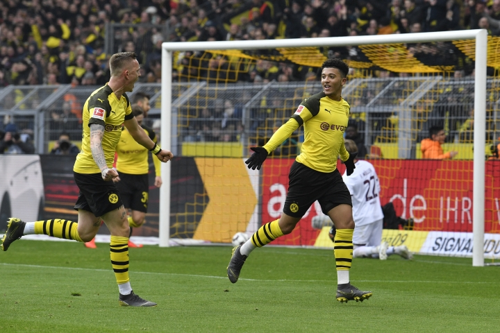 CORRECTS NAME OF THE PLAYER AT LEFT - Dortmund's Jadon Sancho, right, celebrates with teammate Dortmund's Marius Wolf after scoring during the German Bundesliga soccer match between Borussia Dortmund and FSV Mainz 05 in Dortmund, Germany, Saturday, April 13, 2019. (AP Photo/Martin Meissner)