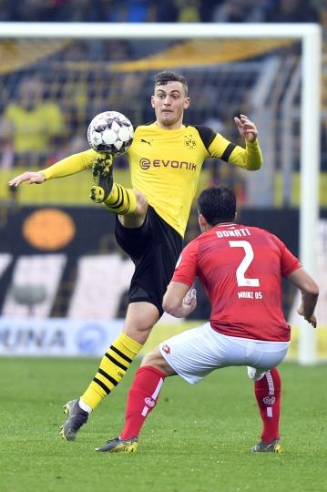 Dortmund's Jacob Bruun Larsen, left, controls the ball past Mainz's Giulio Donati during the German Bundesliga soccer match between Borussia Dortmund and FSV Mainz 05 in Dortmund, Germany, Saturday, April 13, 2019. (AP Photo/Martin Meissner)