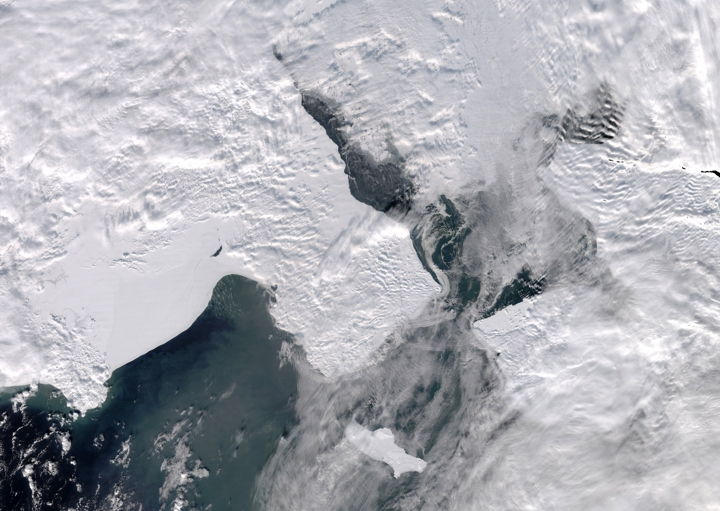 A satellite photo provided by the University of Alaska Fairbanks' Geographic Information Network of Alaska shows clouds partially covering open water in the northern Bering Sea, the Bering Strait and the Chukchi Sea on Monday, March 4, 2019. St. Lawrence Island is in the foreground. Warm winds in mid-February melted or blew off much of the sea ice in the northern Bering Sea, a region historically covered by sea ice throughout the winter. (University of Alaska Fairbanks/Geographic Information Network of Alaska photo via AP)