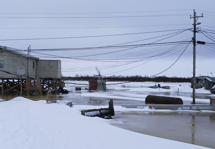 In this Feb. 12, 2019 photo provided by Philomena Keys, high water pushed up the Yukon River from the Bering Sea floods yards around homes in the western village of Kotlik, Alaska. Warm winds in February melted or pushed away Bering Sea ice, leaving coastal villages vulnerable to winter flooding. (Philomena Keys via AP)