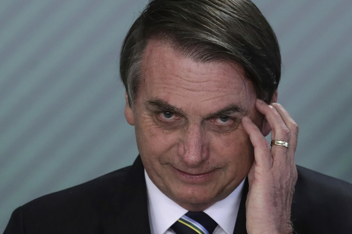 FILE - In this April 9, 2019 file photo, Brazil's President Jair Bolsonaro attends a swearing-in ceremony at the Planalto Presidential Palace, in Brasilia, Brazil. Bolsonaro's administration plans to auction seven oil fields despite contrary advice from analysts of Brazil's main environmental body. (AP Photo/Eraldo Peres, File)