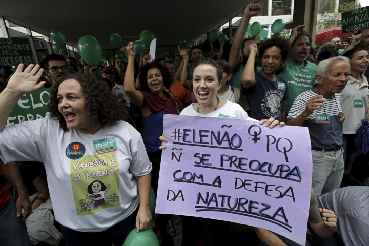 """FILE - In this Oct. 19, 2018 file photo, an environmental activist holds a sign with a message that reads in Portuguese: """"Not him, because he does not care about defending nature,"""" during a protest against then presidential frontrunner Jair Bolsonaro, in Brasilia, Brazil. Bolsonaro's administration plans to auction seven offshore oil fields in the northeast despite contrary advice from from analysts of Brazil's main environmental body. (AP Photo/Eraldo Peres, File)"""