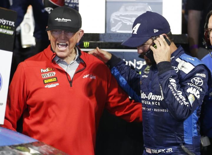 Martin Truex Jr. talks on a phone as he and team owner Joe Gibbs, left, celebrate winning the NASCAR Cup Series auto race at Richmond Raceway in Richmond, Va., Saturday, April 13, 2019. (AP Photo/Steve Helber)