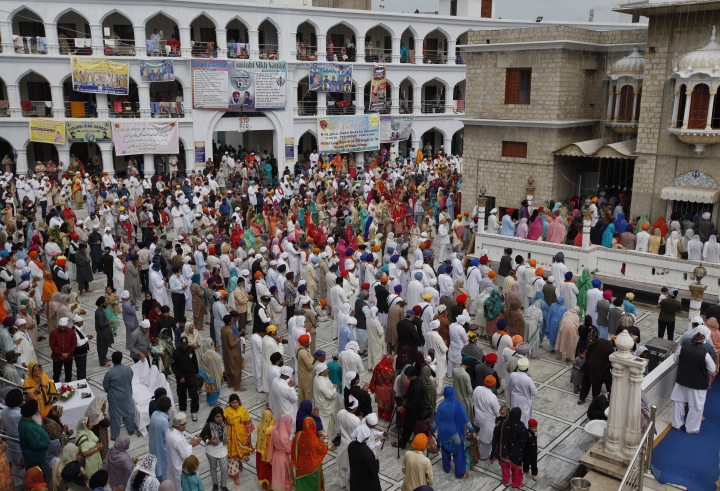 Sikh pilgrims pray during the Vasakhi festival, at the shrine of Gurdwara Punja Sahib, the second most sacred place for Sikhs, in Hasan Abdal, some 50 kilometers (31 Miles) from Islamabad, Pakistan, Sunday, April 14, 2019. Thousands of Sikh pilgrims arrived from neighboring India and other countries to attend the harvest festival that is regionally known by many names and marks the Solar New Year. (AP Photo/Anjum Naveed)