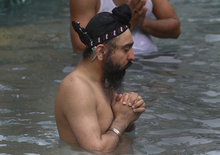 A Sikh pilgrim prays while taking a holy bath during the Vasakhi festival, at the shrine of Gurdwara Punja Sahib, the second most sacred place for Sikhs, in Hasan Abdal, some 50 kilometers (31 Miles) from Islamabad, Pakistan, Sunday, April 14, 2019. Thousands of Sikh pilgrims arrived from neighboring India and other countries to attend the harvest festival that is regionally known by many names and marks the Solar New Year. (AP Photo/Anjum Naveed)