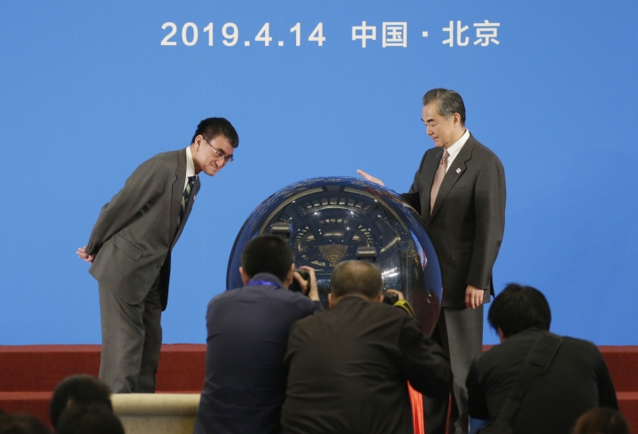 Japanese Foreign Minister Taro Kono, left, and China's Foreign Minister Wang Yi, right, attend an opening ceremony for the Japan-China year of youth exchange at Diaoyutai State Guesthouse in Beijing, China, Sunday, April 14, 2019.(Jason Lee/Pool Photo via AP)