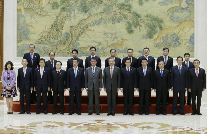 Japanese Foreign Minister Taro Kono, center left, China's Foreign Minister Wang Yi, center right, and members of Chinese and Japanese delegations attend a group photo event before the Japan-China high level economic dialogue at Diaoyutai State Guesthouse in Beijing, China, Sunday, April 14, 2019.(Jason Lee/Pool Photo via AP)