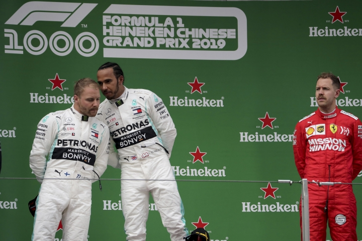 Mercedes driver Lewis Hamilton of Britain, center whispers to teammate Valtteri Bottas of Finland as Ferrari driver Sebastian Vettel of Germany at right waits for the award ceremony for the Chinese Formula One Grand Prix at the Shanghai International Circuit in Shanghai on Sunday, April 14, 2019. (AP Photo/Ng Han Guan)