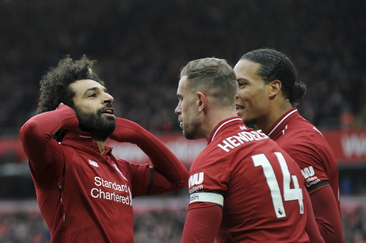 Liverpool's Mohamed Salah, left, celebrates with teammates after scoring his side's second goal during the English Premier League soccer match between Liverpool and Chelsea at Anfield stadium in Liverpool, England, Sunday, April 14, 2019. (AP Photo/Rui Vieira)