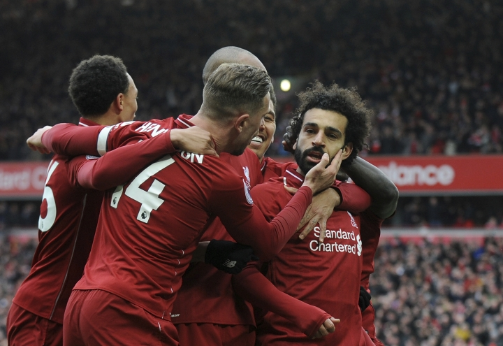 Liverpool's Mohamed Salah, right, celebrates with teammates after scoring his side's second goal during the English Premier League soccer match between Liverpool and Chelsea at Anfield stadium in Liverpool, England, Sunday, April 14, 2019. (AP Photo/Rui Vieira)