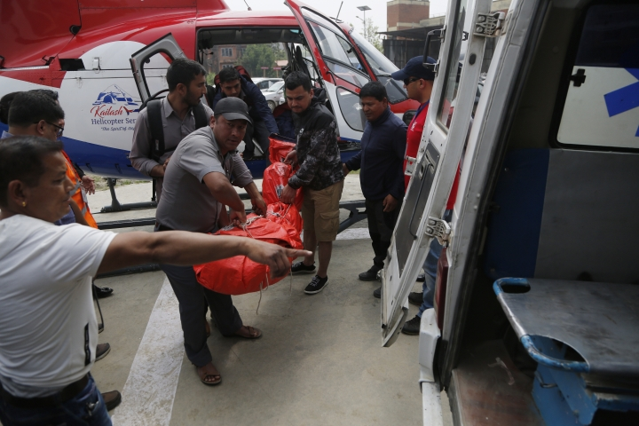 Hospital officials unload the dead body of a plane crash victim outside the Teaching Hospital in Kathmandu, Nepal, Sunday, April 14, 2019. At least three people were killed and four injured on Sunday after a small plane crashed into a parked helicopter during takeoff at the only airport in Nepal's Everest region. (AP Photo/Niranjan Shrestha)
