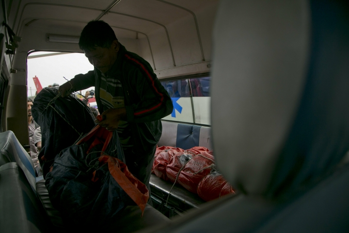 A hospital official loads a dead body of a plane crash victim into an ambulance outside the Teaching Hospital in Kathmandu, Nepal, Sunday, April 14, 2019. At least three people were killed and four injured on Sunday after a small plane crashed into a parked helicopter during takeoff at the only airport in Nepal's Everest region. (AP Photo/Niranjan Shrestha)