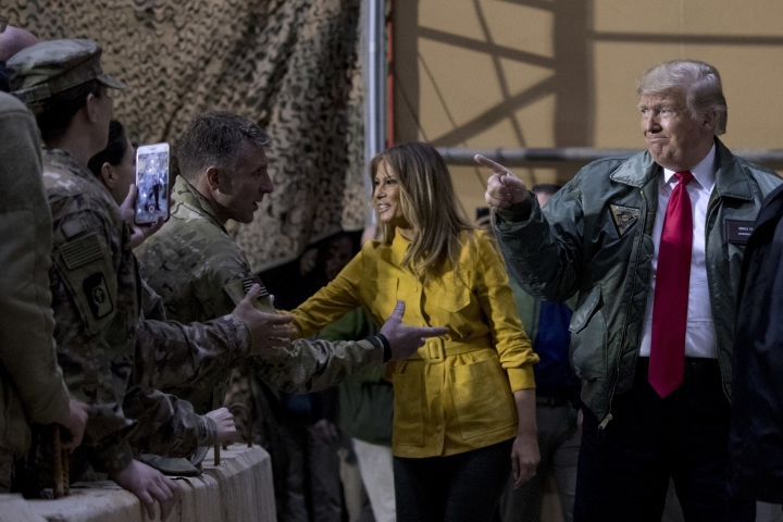 FILE -- In this Dec. 26, 2018 file photo, President Donald Trump and first lady Melania Trump greet members of the military at a hangar rally at Al Asad Air Base, Iraq. Iraq is seeking to reclaim a leadership role in the Arab world after decades of conflict. It is focusing on a centrist policy and its top leaders are determined to maintain good relations with both Iran and the United States. (AP Photo/Andrew Harnik, File)