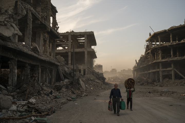 FILE - In this Nov. 15, 2017 file photo, Haider, left, and Abdullah carry belongings they collected from their damaged house to wash before returning to live in the Old City of Mosul, Iraq. A flurry of recent diplomatic activity and high-profile visits to the Iraqi capital, points to a new era of openness as the nation sheds its war image and re-engages with the world. Iraq needs much help and investment to rebuild its cities -- something it can only get from oil- and gas-rich Gulf countries, including Saudi Arabia. (AP Photo/Felipe Dana, File)