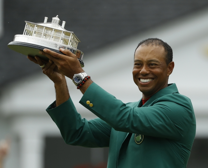 Tiger Woods wears his green jacket holding the winning trophy after the final round for the Masters golf tournament Sunday, April 14, 2019, in Augusta, Ga. (AP Photo/Matt Slocum)