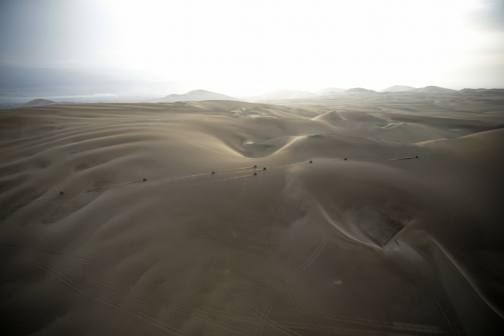 "FILE - In this Jan. 16, 2019 photo, competitors ride their motorbikes across the dunes during stage nine of the Dakar Rally in Pisco, Peru. Dakar organizers say next year's cross-country race will be held in ""the deep and mysterious deserts of the Middle East, in Saudi Arabia."" (AP Photo/Ricardo Mazalan, File)"