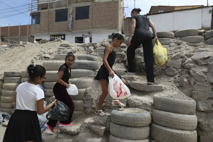 In this April 4, 2019 photo, Maria del Carmen Silva, a former professional dancer, and her ballet students, search and collect recycling plastic bottles for money, in the Chorrillos neighborhood, a poor part of Lima, Peru. If they can raise enough money for plane tickets. Silva hopes to take her students to Florida to participate in a dance competition later this year. (AP Photo/Martin Mejia)