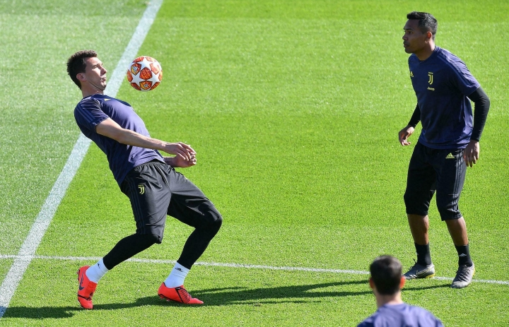 Juventus' Mario Mandzukic, left, and Alex Sandro attend a training session ahead f Tuesday's Champions League, quarter final second leg soccer match between Juventus and Ajax, at the Juventus training center, near Turin, Italy, Monday, April 15, 2019. (Alessandro Di Marco/ANSA via AP)