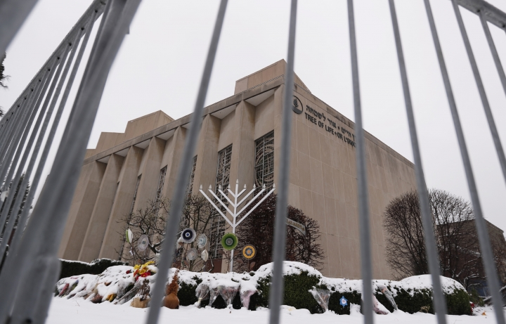 "FILE--This file photo from Feb. 11, 2019 shows a temporary barrier around the Tree of Life Synagogue in Pittsburgh where 11 people were killed and seven others injured during an attack on in October of 2018. The synagogue is inviting young people worldwide to submit artwork in an art project called ""#HeartsTogether: The Art of Rebuilding."" to cover adjacent fencing that surrounds the still-shuttered building. They are looking for ""original, uplifting images and graphics"" to be printed on windscreens that will cover the temporary perimeter fencing. (AP Photo/Keith Srakocic, File)"