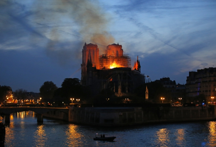 Firefighters tackle the blaze as flames and smoke rise from Notre Dame cathedral as it burns in Paris, Monday, April 15, 2019. Massive plumes of yellow brown smoke is filling the air above Notre Dame Cathedral and ash is falling on tourists and others around the island that marks the center of Paris. (AP Photo/Michel Euler)