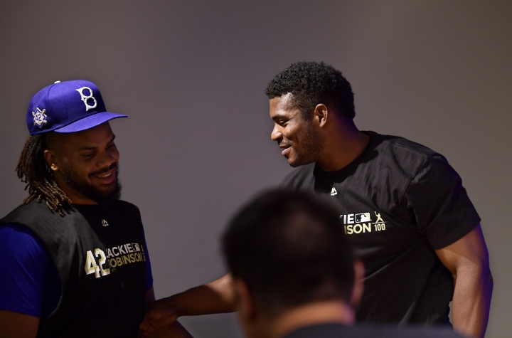 Cincinnati Reds' Yasiel Puig, right, is greeted by Los Angeles Dodgers relief pitcher Kenley Jansen as Puig speaks to reporters prior to a baseball game between the Dodgers and the Reds, Monday, April 15, 2019, in Los Angeles. (AP Photo/Mark J. Terrill)