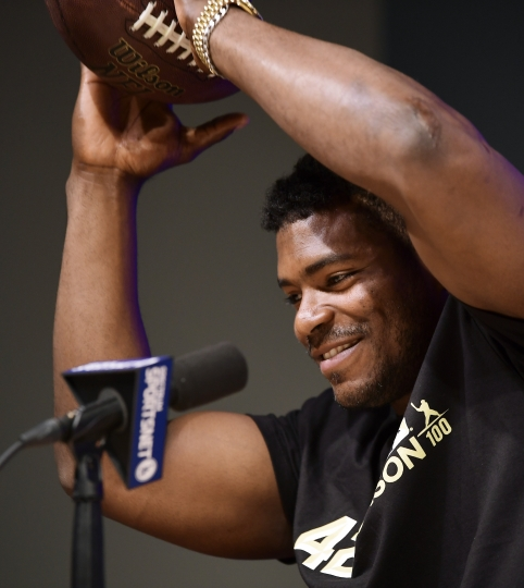 Cincinnati Reds' Yasiel Puig catches a football thrown by Los Angeles Dodgers relief pitcher Kenley Jansen as he speaks to reporters prior to a baseball game between the Dodgers and the Reds, Monday, April 15, 2019, in Los Angeles. (AP Photo/Mark J. Terrill)