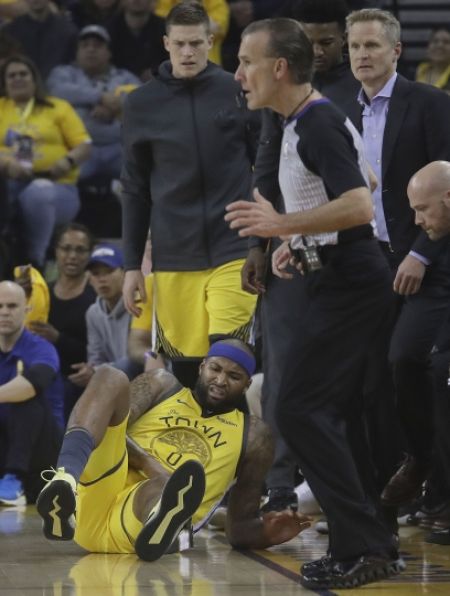 Golden State Warriors center DeMarcus Cousins, bottom, reacts after falling to the floor during the first half of Game 2 of a first-round NBA basketball playoff series against the Los Angeles Clippers in Oakland, Calif., Monday, April 15, 2019. (AP Photo/Jeff Chiu)