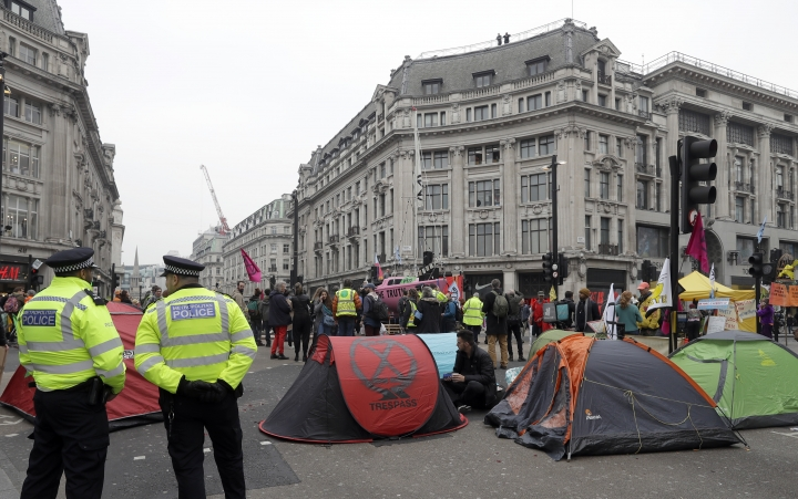 Police stand guard as demonstrators camp on the road during a climate protest in Oxford Circus in London, Tuesday, April 16, 2019. The group Extinction Rebellion is organizing a week of civil disobedience against what it says is the failure to tackle the causes of climate change. (AP Photo/Kirsty Wigglesworth)