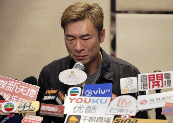 Hong Kong singer Andy Hui reacts during a press conference about his affair in Hong Kong, Tuesday, April 16, 2019. Hong Kong's Apple Daily newspaper published video that purported to show Andy Hui being intimate in a taxi with another Hong actress, decades younger than him, Jacqueline Wong. (AP Photo/Vincent Yu)